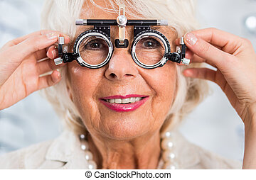 Senior woman in opticians office having examined sight