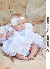 lovely baby girl in a beautiful white dress lying on a sofa.