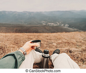 POV image of traveler with thermos - Traveler man sitting...