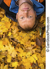Young man lying on yellow leaves.