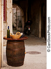 Wine bottles with bread on the top of the barrel in Trogir,...