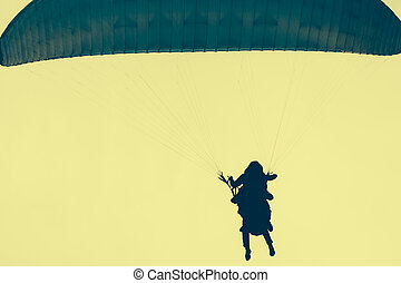 Silhouettes of skydivers in a yellow sky