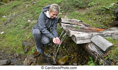 Girl drinks water from a mountain spring