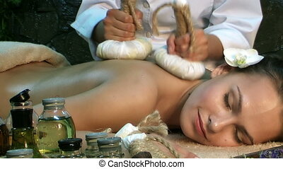 Woman Receiving thai hot herbal ball massage in spa. - Girl...