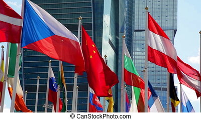Different countries flags waving near skyscraper - Many...