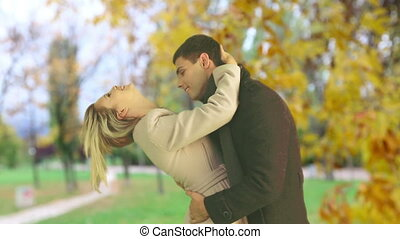Man and woman kissing beautiful in autumn park outdoor. -...