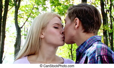 Young couple kissing and flirting in park. - Close up of...