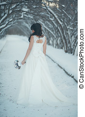 Beautiful bride with a bouquet in winter