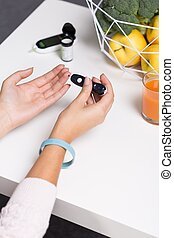 Female with pen glucometer - Image of female controlling...