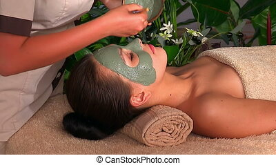 Beautician apply mask on face of girl - Clay facial mask in...