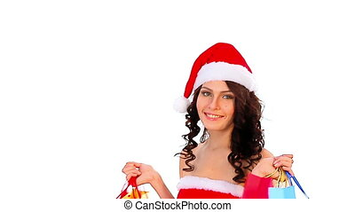 Woman in Santa hat holding shopping bag. Girl give big red...