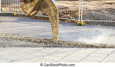 Excavator Ripping Asphalt with fence behind it