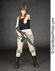 Young woman armed with rifle standing on black background