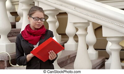 woman in a red scarf leafing through the book