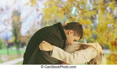 Man and woman kissing madly beautiful in the autumn park -...