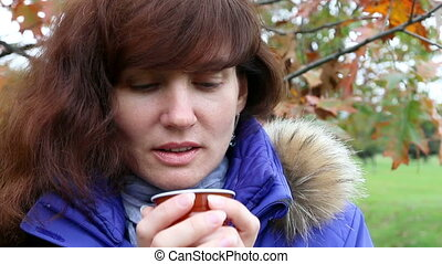 Woman drink coffee in autumn park.Outdoor - Chilled but...
