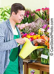 Florist working in flower shop watering plants