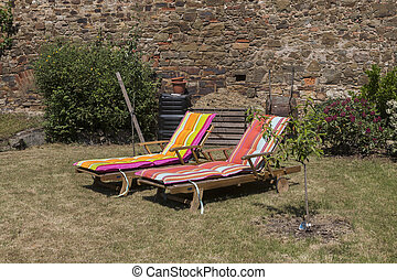 Two lawn chairs on the sun-drenched garden