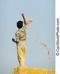 Indian boy flying kite from the roof of traditional house in...