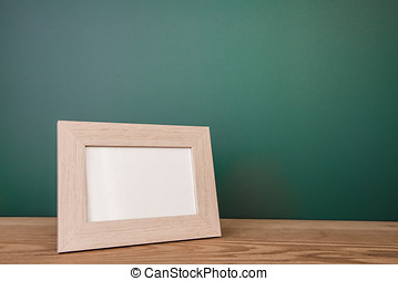 Vintage photo frame on wooden table over green background,...