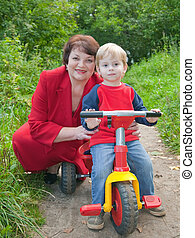 grandmother with boy on tricycle at nature