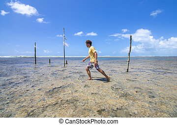 Trekking across coral reefs in Brazil - Caucasian male...