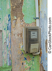 Old electricity meter very unsafely fit on a peeling wall