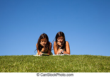 Reading at the park - two young sisters at the park reading...