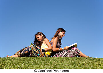 Learning and enjoying nature - two young sisters reading...