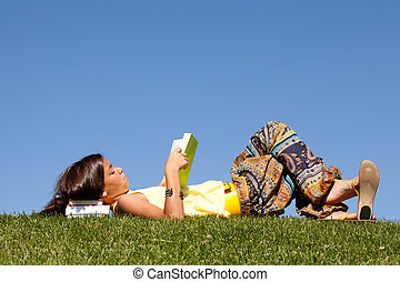 Children reading a book - little girl relaxing at the top of...