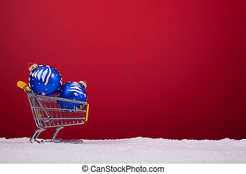 Shopping season - christmas balls in a shopping cart over a...