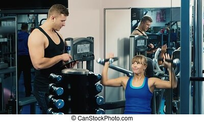 Attractive woman trained in the gym with a personal trainer