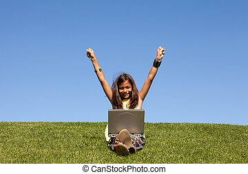 gilr using wireless internet at the park - Young girl using...