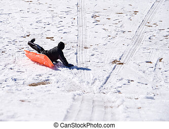 Sledding Accident - A young boy tumbling off of his sled.
