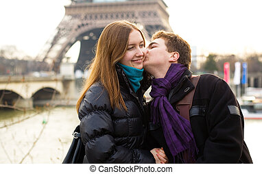 Happy loving couple near in Paris kissing near the Eiffel...