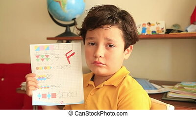 Unhappy little student holding school paper with F grade