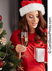 young woman by a christmastree and champagner