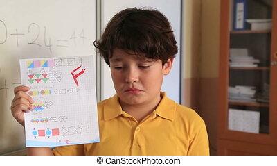 Impassive schoolboy - Brat schoolboy holding school paper...
