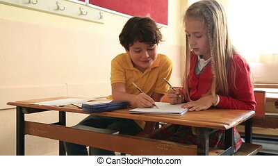 Smiling pupils working together in a classroom
