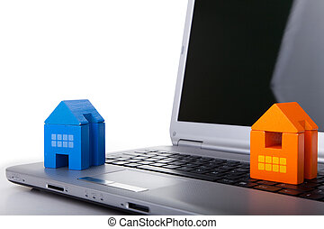 House toy over a laptop - using the internet to find a house