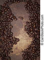 Dark brown roasted coffee beans on a shabby chic surface