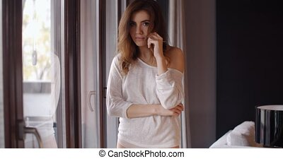 Beautiful Girl Standing Next to Big Window in Her Living...
