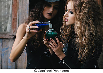 Two vintage witches perform magic ritual, with elixir in...