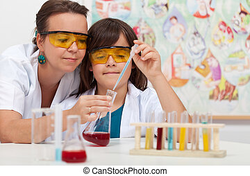 Young boy in elementary science class doing chemical experiment