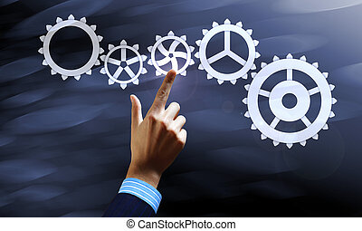 Gears mechanism Concept image - Close up human hand pointing...
