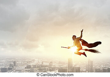 Businessman on broom - Young businessman flying high above...
