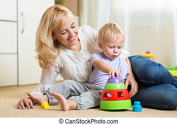 mother and her child playing with colorful logical toy -...