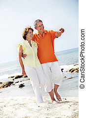 Happy mature couple walking along the beach