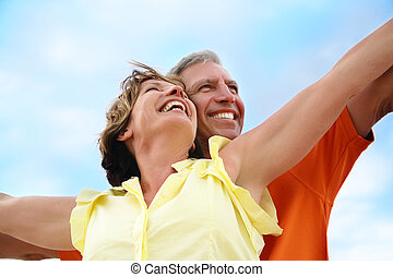 Happy mature couple standing with arms outstretched