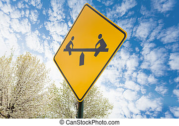 Teeter-totter yellow sign on sky background in Salt Lake...